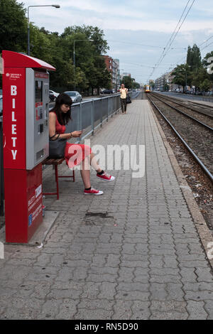 Woman in a red dress with red shoes sitting on a train platform next to a red ticket machine - Stock Photo
