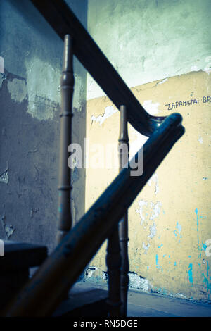 Wooden bannister turning a corner in a derelict apartment building - Stock Photo
