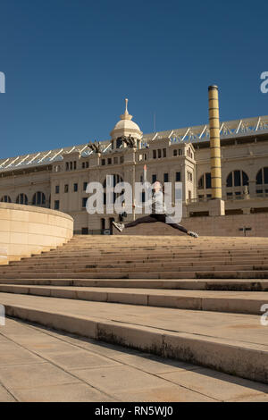 A young attractive girl makes a dance jumps leap along the staircase leading to the 'Estadi Olímpic Lluís Companys', Barcelona, Spain - Stock Photo