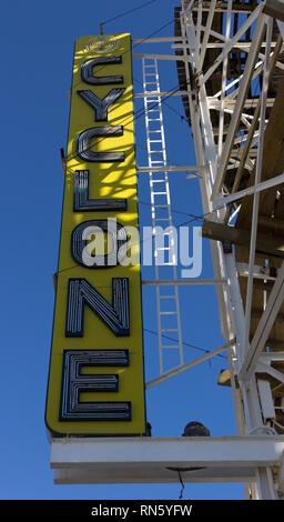 New York, USA. 16th February, 2019. Sun splashes onto the yellow, white, and blue Cyclone sign through the historic slats of this Surf Avenue wooden roller coaster at Luna Park at Coney Island in Brooklyn, on a blue-sky winter day in February. Originally built in 1927, this thrill ride was saved from demolition and later placed on the New York State Register of Historic Places in 1991. Recognized as an ACE Roller Coaster Landmark by the American Coaster Enthusiasts, the Cyclone has served as a backdrop for weddings, movies, and world-record riding marathons. Kay Howell/Alamy Live News - Stock Photo