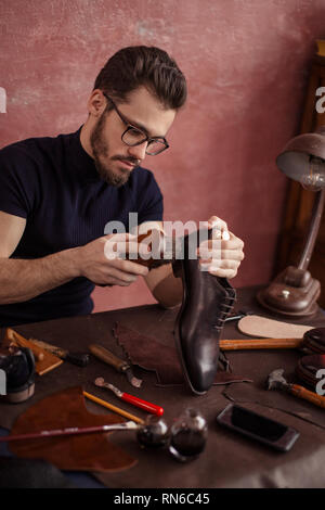 guy using the brush for footwear. close up photo - Stock Photo
