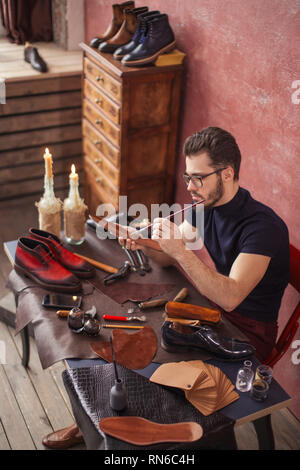 attractive guy in glasses smears special liquid with a brush . side view photo - Stock Photo
