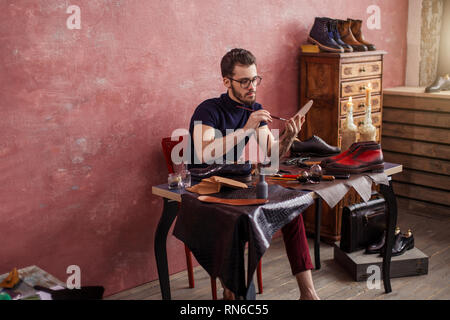 hardworking designer using stain in the shoe shop. close up side view photo - Stock Photo