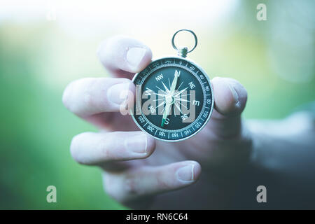 Young man on an adventure is holding a compass in his hand for finding is route - Stock Photo