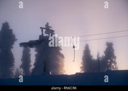 Silhouette of ski lift and trees at winter with sunrays through mist in  Levi ski resort in Kittilä, Finland - Stock Photo