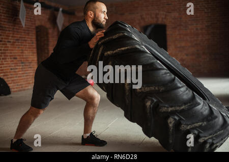 CrossFit Tire Technique. Powerful bodybuilder demonstrates rules and order of training with improvised powerlifting element in fitness club - Stock Photo