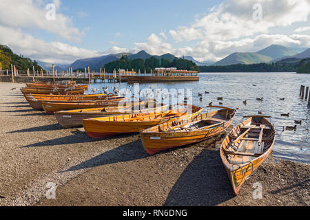 Row of wooden row boats lined up on the shore of Derwent water, Keswick, Cumbria. - Stock Photo