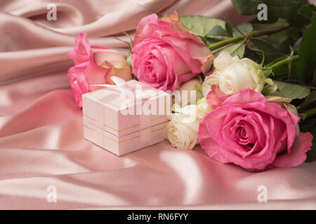 Gift box with silk ribbon and flowers on a gentle pink satin background. Festive concept. - Stock Photo