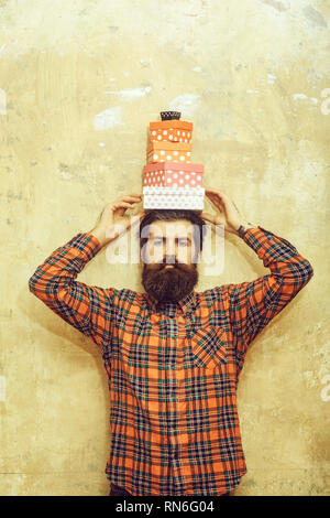 serious bearded man holding colorful gift boxes stacked on head - Stock Photo