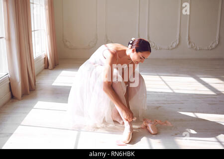 Ballerina wearing pointe shoes in the room - Stock Photo