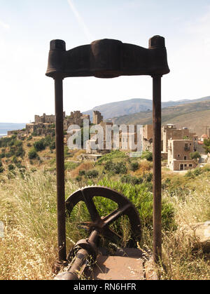 Old rusty mechanism with gear and the medieval village of Vathia in Mani, Greece. - Stock Photo