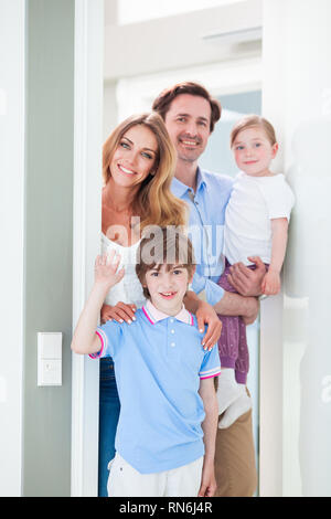 Portrait of happy smiling family with little children in doorway - Stock Photo