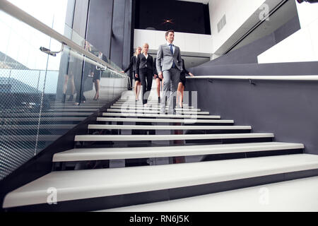 Group of business people walking and taking at stairs in an office building - Stock Photo