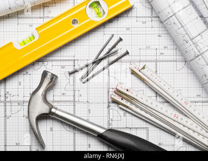 Construction tools  with hammer, nails, folding rule and level on architectural blueprint plan background flat lay top view from above - Stock Photo