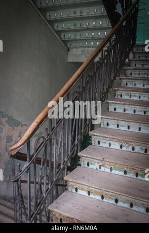 wooden staircase in daylight with worn treads in a tenement house - Stock Photo