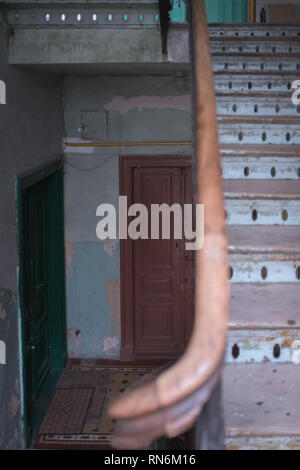 two front doors in a run down tenement house with a a wooden staircase leading to other floors - Stock Photo
