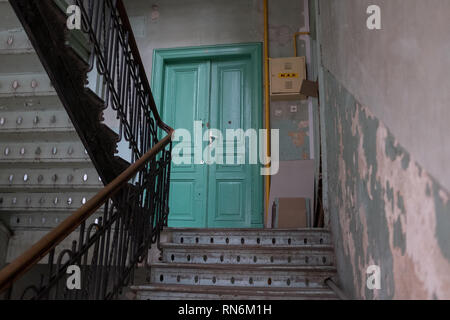 Period wooden staircase for an apartment block leading to a green door - Stock Photo