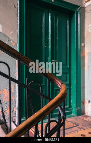 Period staircase for an apartment block leading to a green door - Stock Photo