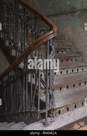 curve of a wooden staircase in a tenement block which is very tatty and old - Stock Photo