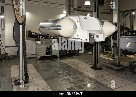 A small white rubber motorboat raised on a car lift for cleaning and repairs in a vehicle repair and maintenance workshop - Stock Photo
