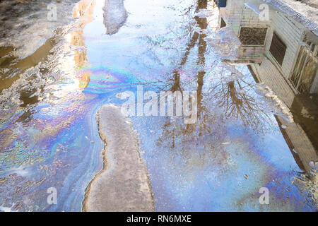 puddle from melting snow with rainbow streaks from spilled engine oil on road in city in spring day - Stock Photo