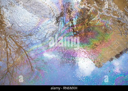 rainbow spots from spilled engine oil in puddle from melting snow on road in city in spring day - Stock Photo