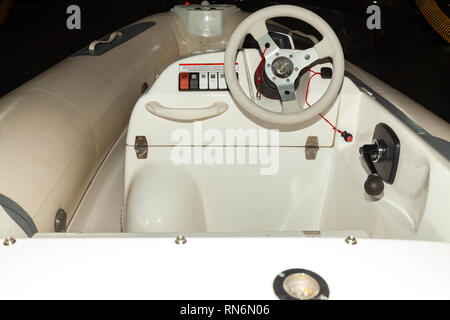 A close-up view of the steering wheel of a small white rubber motorboat with cockpit and control buttons on the dashboard - Stock Photo
