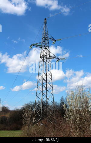 Tall metal electrical power line utility pole made of strong metal pipes with multiple electrical wires connected with glass insulators - Stock Photo