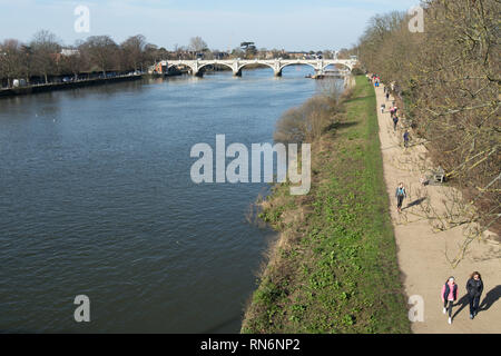 view towards richmond lock from twickenham bridge, with sunday afternoon walkers beside the river thames - Stock Photo