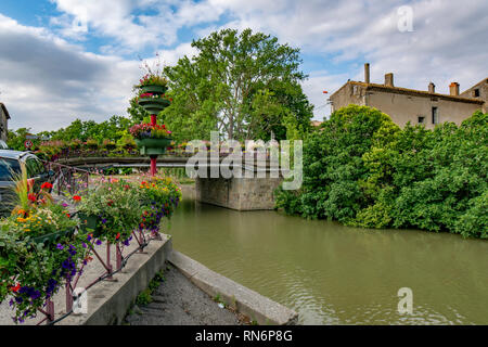 Trebes, France; June 2017: view of the bridge adorned with flowers crossing the Canal Midi in the village of Trebes - Stock Photo