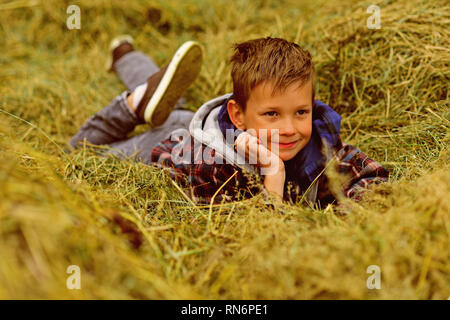 Relax, take it easy. Small kid relax in hay. Small kid daydreaming in farm barn. Relax the whole day - Stock Photo