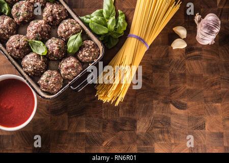 Raw feef meat balls basil tomato sauce garlic and spaghetti on butcher board. - Stock Photo