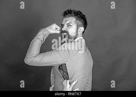 Angry guy bought counterfeit or fake brand. Man with beard wears jacket with hole on dark background. Hipster chose small size jacket, seam torn with - Stock Photo