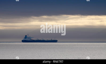 Commercial ship anchored off the coast - Stock Photo