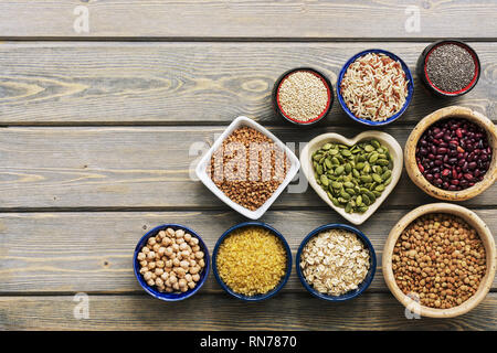 A set of various superfoods - whole grains,beans, seeds, legumes in bowls on a wooden plank table. Top view, copy space - Stock Photo