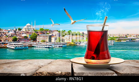 Tea in Golden Horn bay of Istanbul and view on Suleymaniye mosque, Turkey - Stock Photo