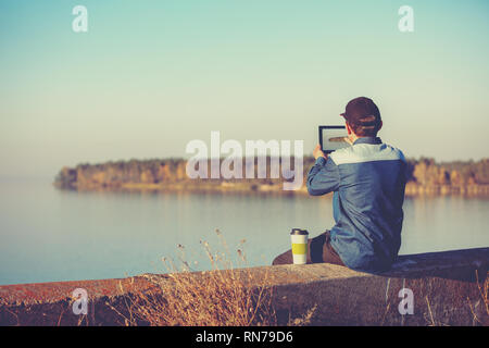 A man sits on the concrete embankment of a picturesque lake in evening. The man takes a photo of lake with a tablet - Stock Photo