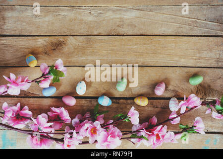Cherry blossom Artificial flowers and easter egg on vintage wooden background with copy space. - Stock Photo