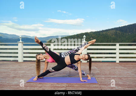 Beautiful, slender girls practicing sretching together. Flexible women doing yoga on yoga mat outdoors on fresh air in mountains. Wellbeing and nature concept. - Stock Photo