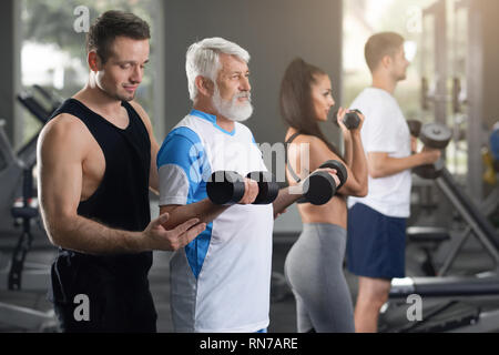 Horizontal closeup view of men and woman on daily training in gym. Young sporty attractive man helping another man going exercises with weights. Senior adult in white t-shirt exercising. - Stock Photo