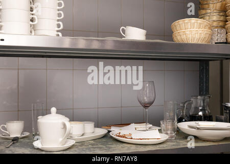 Dirty dishes, wine glasses, plates, cups on a metal rack in the restaurant's kitchen - Stock Photo