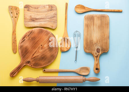 Kitchen utensils, food preparation cooking accessorises, chopping boards, wooden spoons, whisk on blue and yellow table, top view, selective focus - Stock Photo