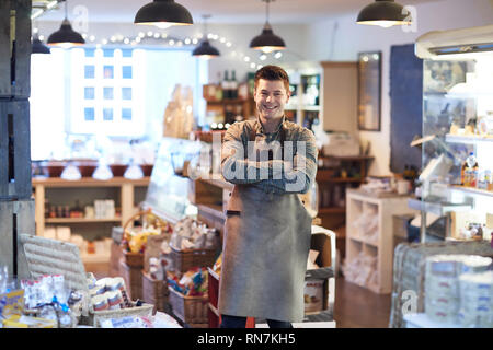 Portrait Of Smiling Male Owner Of Delicatessen Shop Wearing Apron - Stock Photo