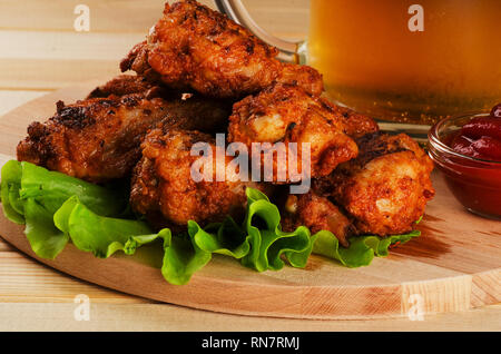 Crispy chicken wings in breadcrumbs with sause and beer on a cutting board - Stock Photo