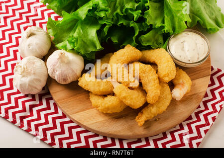 Fried organic coconut shrimp in breading with cocktail sauce and salad - Stock Photo