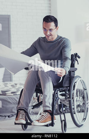 Professional occupation. Joyful smart engineer looking at the blueprint while sitting in the wheel chair - Stock Photo