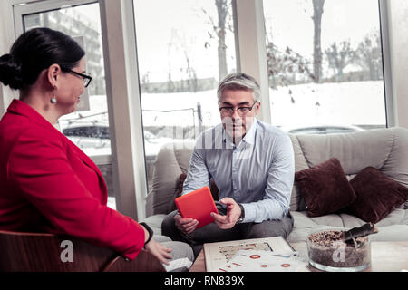 Adult grey-haired businessman in eyeglasses discussing new information with his partner