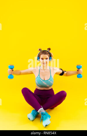 Woman wearing bright leggings and short top working out - Stock Photo