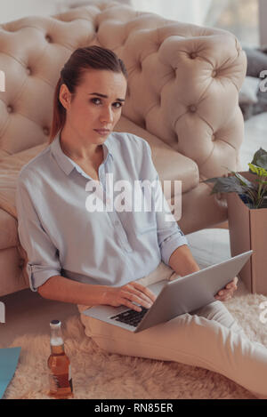 Eyes full of sorrow. Upset young freelancer looking at you with sadness while holding a laptop on her knees and sitting on the floor of her apartments - Stock Photo