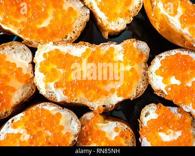 russia cuisine - top view of sandwiches with butter and red caviar on black plate close up - Stock Photo